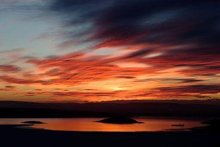 going down: Una puesta de sol de oro a la baja detr�s de una colina sobre un lago congelado - fiordo. Fiordo de Oslo en marzo.  Foto de archivo