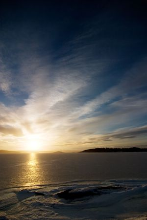 A golden sunset going down behind a hill over a frozen lake - fjord.  Oslo fjord in March. photo