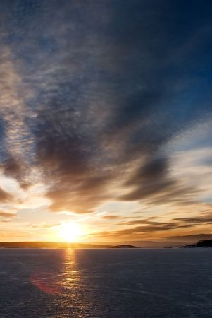 A golden sunset going down behind a hill over a frozen lake - fjord.  Oslo fjord in March. Stock Photo - 774592
