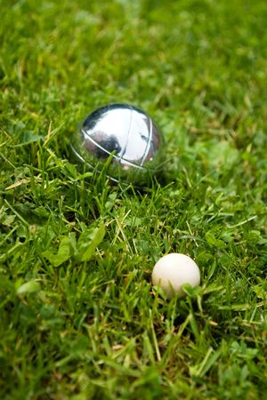 boules: Bocce balls sitting in the green grass, close to the target. -shallow depth of field.- Stock Photo