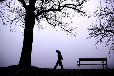 A person walking alone in thick fog. photo