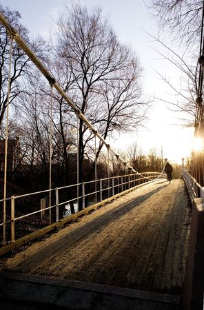 A beautiful day with the sun shinning into the camera over a suspension bridge. Stock Photo - 774517