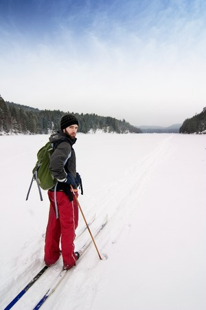 A cross country skier out on a refreshing trip over a frozen lake. photo