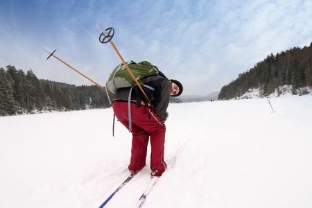 A cross country skiier vorgibt zu sein Rennen auf einem zugefrorenen See.