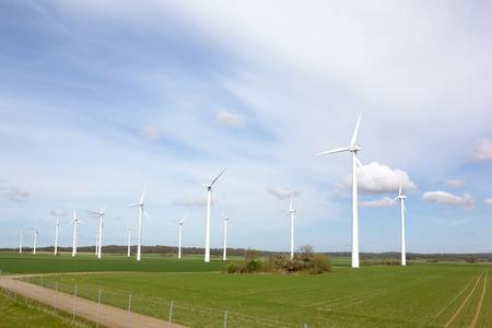 capturing: Windmill on a flat landsacpe capturing engergy against a blue sky Stock Photo