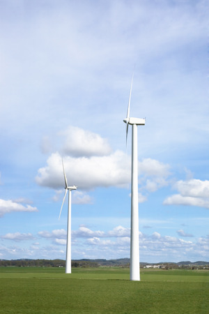 open source: Windmill on a flat landsacpe capturing engergy against a blue sky Stock Photo