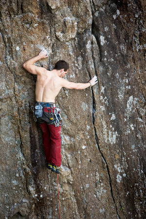 A male climber against a large rock face climbing lead. photo