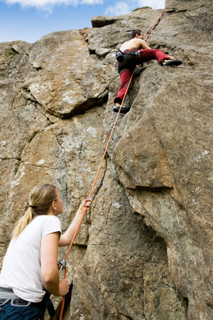 rock bottom: A female belaying a male on a steep rock face.  Shallow depth of field with the focus on the climbing which is belaying (the on at the bottom) Stock Photo