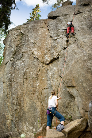 A female belaying a male on a steep rock face. Stock Photo - 1543517