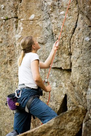 belaying: A female belaying a climbing outdoors