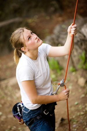 A female belaying a male on a steep rock face.  Shallow depth of field has been used to isolated the belayer, with focus on the eyes and head. photo
