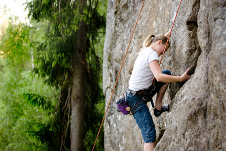 the crag: A female climber, climbing using a top rope on a steep rock face (crag) Stock Photo