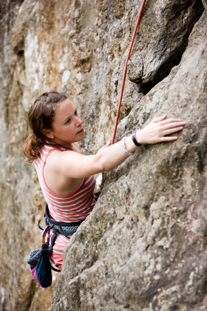 the crag: A female climber, climbing using a top rope on a steep rock face (crag).  A shallow depth of field has been used to isolated the climber, with the focus on the head and eyes.