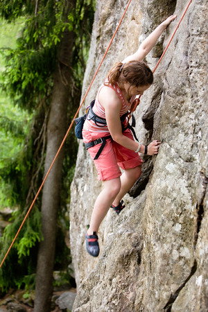 the crag: A female climber, climbing using a top rope on a steep rock face (crag).  A shallow depth of field has been used to isolated the climber, with the focus on the head and right hand.
