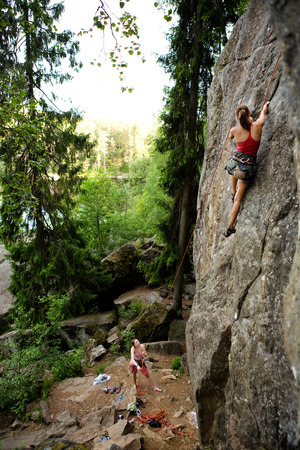 A female climber, climbing using a top rope on a steep rock face (crag) Stock Photo - 1543509