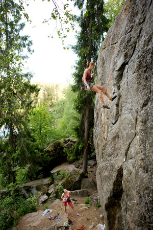 repelling: A female climber, repelling down a steep rock face (crag)