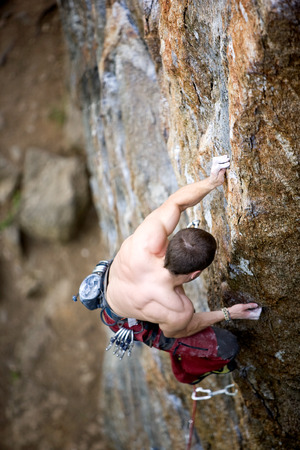 the crag: A male climber, viewed from above, climbs a very high and steep crag. Shallow depth of field is used to isolate the climber with focus on the hands and head