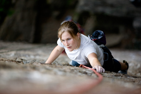 A female climber on a steep rock face looking for the next hold.  Shallow depth of field is used to isolate the climber. Stock Photo