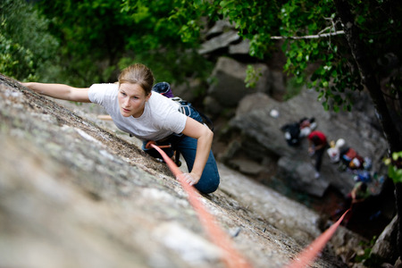 A female climber on a steep rock face.  Shallow depth of field is used to isolated the climber.  Focus is on the head, shoulders and arms of the climber. photo