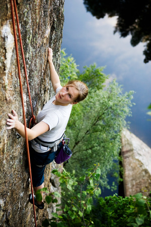 A female climber on a steep rock face looking for the next hold.  Shallow depth of field is used to isolate the climber. Stock Photo - 1543487