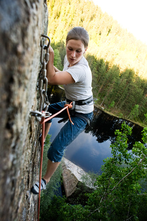 A climber at the top of a ledge looking down with fear. photo