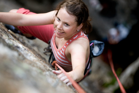 A female climber on a steep rock face viewed from above with the belayer in the background.  The climber is smiling at the camera. Shallow depth of field is used to isolated the climber. photo