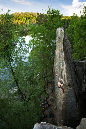 the crag: A male climber, viewed from above, climbs a very high and steep crag. A beautiful lake and landscape create a breathtaking backdrop. Stock Photo