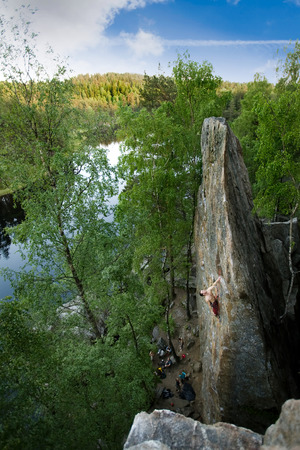 A male climber, viewed from above, climbs a very high and steep crag. A beautiful lake and landscape create a breathtaking backdrop. photo