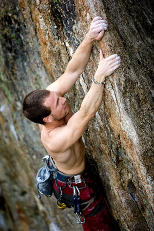 A male climber, viewed from above, climbs a very high and steep crag.  photo