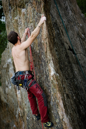 A male climber, viewed from above, climbs a very high and steep crag.  The image is taken as the climber clips into the bolt. photo
