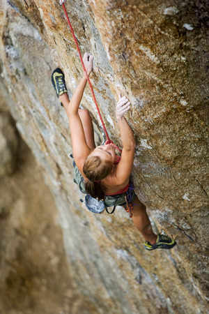 An eager female climber on a steep rock face looks for the next hold - viewed from above.  Shallow depth of field is used to isolated the climber with the focus on the head. Stock Photo - 1543494