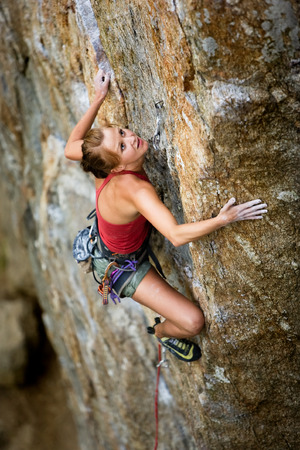 struggling: An eager female climber on a steep rock face looks for the next hold - viewed from above.  Shallow depth of field is used to isolated the climber. Stock Photo