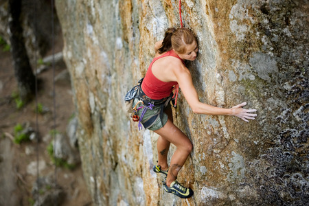 An eager female climber on a steep rock face looks for the next hold - viewed from above.  Shallow depth of field is used to isolated the climber with the focus on the head. Stock Photo - 1543486