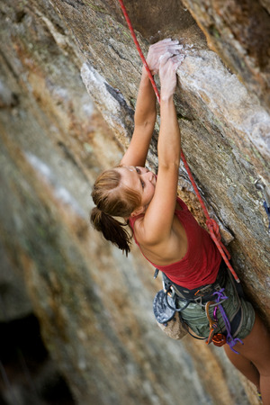 An eager female climber on a steep rock face looks for the next hold - viewed from above.  Shallow depth of field is used to isolated the climber with the focus on the head. photo