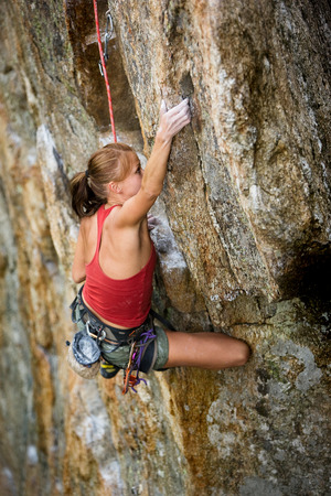 An eager female climber on a steep rock face looks for the next hold - viewed from above.  Shallow depth of field is used to isolated the climber with the focus on the head. Stock Photo - 1543425