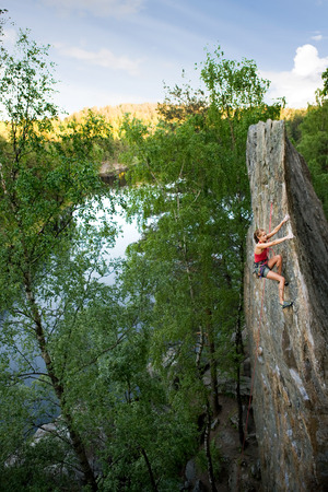 An eager female climber on a steep rock face looks for the next hold. Breathtaking scenery including a lake and forest are in the background. Shallow depth of field is used to isolated the climber with the focus on the head. photo