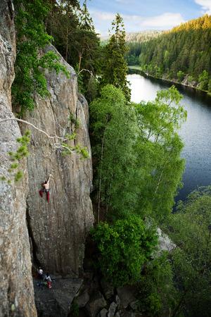 A male climber against a large rock face climbing lead against a magnificant landscape. photo