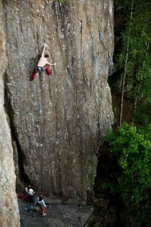 A male climber against a large rock face climbing lead. Stock Photo - 1543507