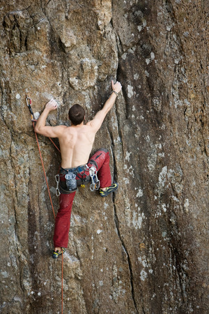 A male climber against a large rock face climbing lead against a magnificant landscape. photo