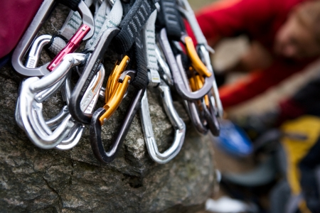 A pile of quick draw carabiners with climbers out of focus in the background. photo