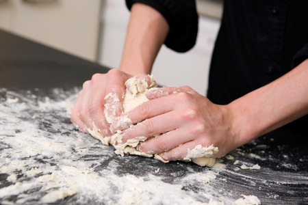 A young woman makes bread on the counter at home in the kitchen. Stock Photo - 1720588