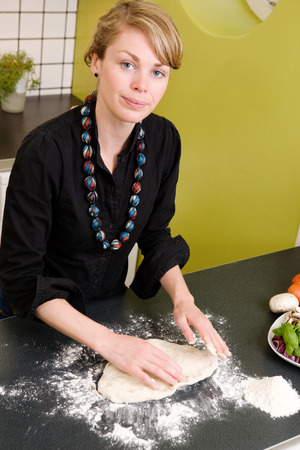 A young woman is making pizza dough on the kitchen counter at home in her apartment. photo