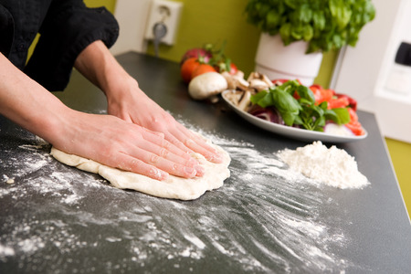A pair of female hands prepare some bread dough on the counter for pizza. photo