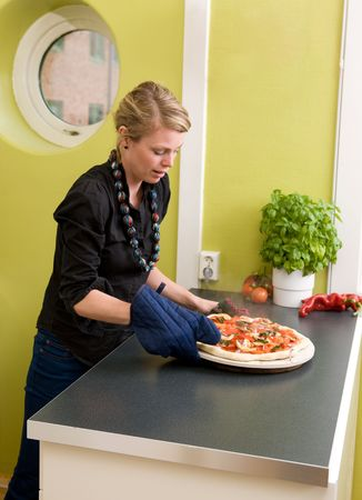 A young woman takes a fresh pizza out of the oven in her apartment kitchen. photo