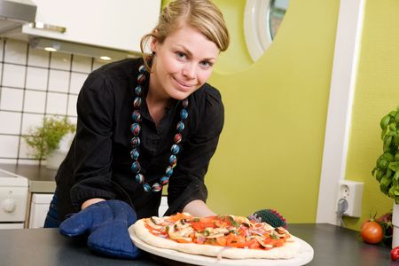 A young woman smiles at the camera with a fresh homemade pizza out of the oven in her apartment kitchen. photo