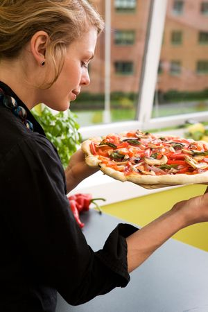 A young woman presents a homemade italian style pizza fresh from the oven in her apartment kitchen. photo
