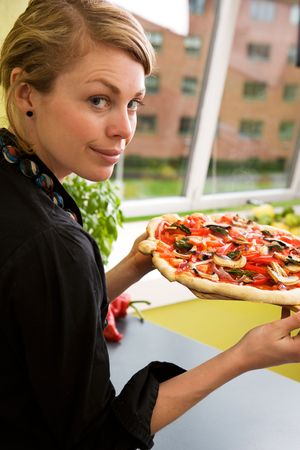 A young woman presents a homemade italian style pizza fresh from the oven in her apartment kitchen. Stock Photo - 1735470