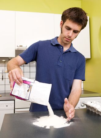 durum: A young man making pasta at home in an apartment kitchen.