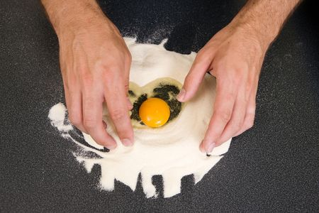 semolina pasta: A young man making pasta at home in an apartment kitchen.  An above view of an egg in flour ready to be mixed by hand.