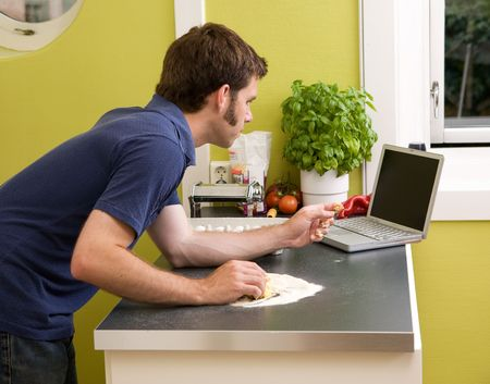 A young cook at home in an apartment kitche, looking on the computer at a recipe while making fresh pasta. photo